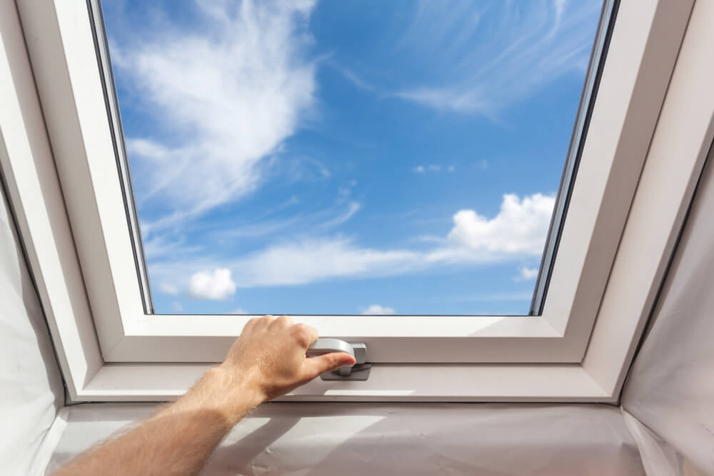 A view of a skylight window from the inside of a home. A man's hand and arm can be seen turning the handle that opens the window. A blue sky and a few clouds can be seen out of the window.