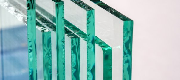 A shot of several vertical sheets of tempered glass in a line. The view of them is from the side.