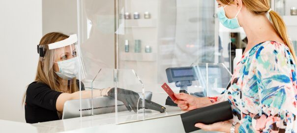 A blonde girl with a mask goes to pay for an item at a white checkout counter. The woman behind the counter uses a face shield and a mask, and plexiglass separates the two.