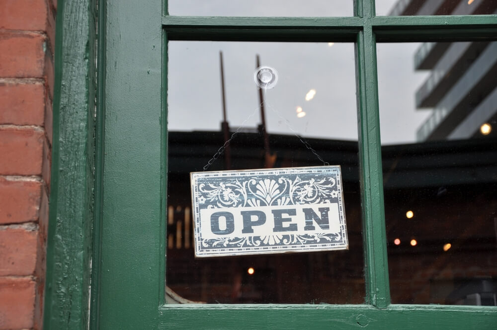 A green-bordered storefront window with an open sign hanging in the window. The sign is dark green with several patterns above it.