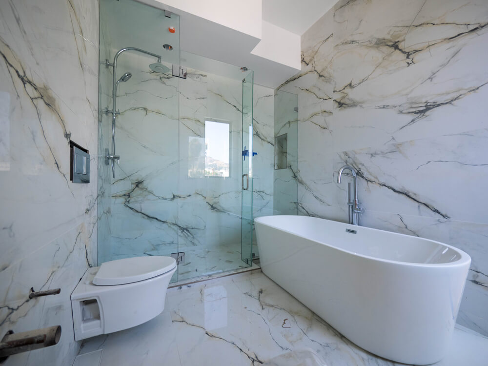 A tiled bathroom with a bathtub on the right, toilet on the left, and a shower with a custom glass enclosure in the middle.