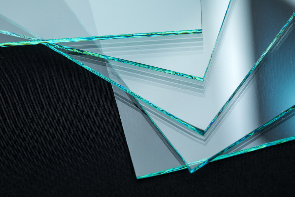 Several sheets of insulated glass are stacked on top of each other on a black surface.