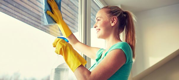 A woman in a blue top and yellow gloves smiles as she wipes a blue cloth on a window to clean it.